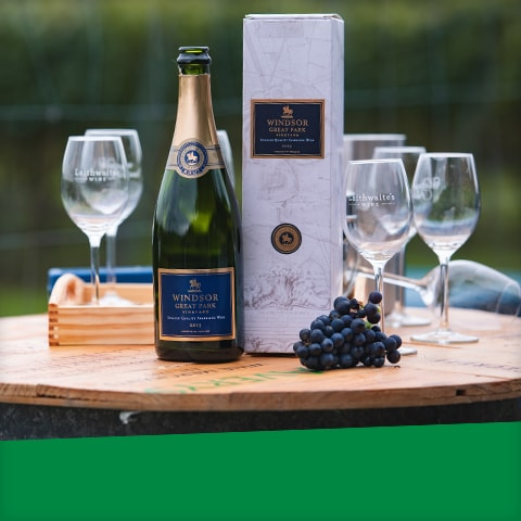 Champagne glasses, a bunch of grapes and an open bottle of Windsor Great Park Champagne
