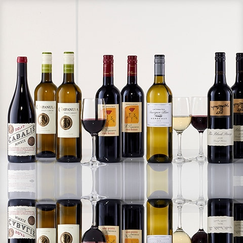 A mixture of red and white wine bottles and glasses of wine