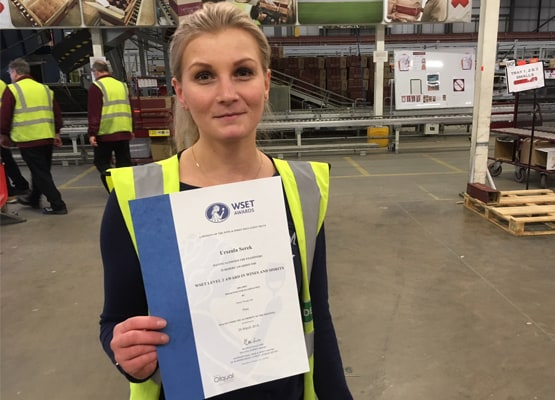 Lady in a warehouse holding up her WSET certificate